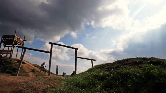 Skillful mountain bike cyclists practicing on extreme terrain against the sky. video