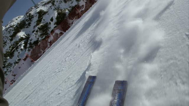 POV Skis leaving a snow powder trail behind them video