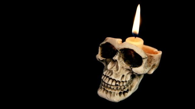 skull with a burning candle on a black background video