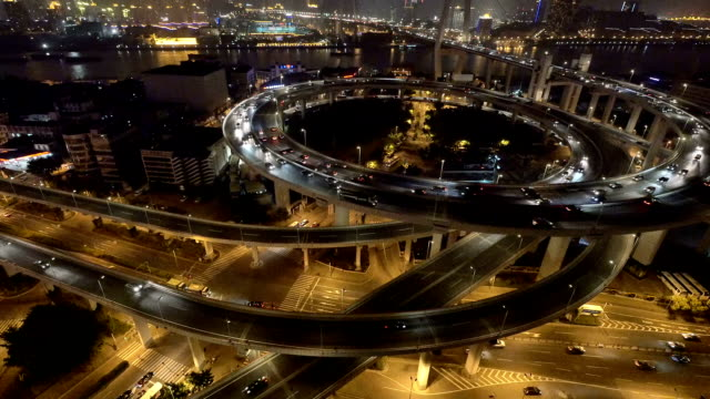 skyline and busy traffic on elevated road intersection at night, real time. video