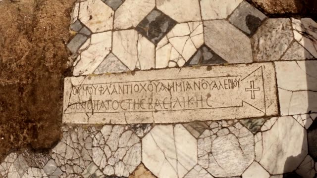 Slab with inscription on ancient Greek and image of cross on floor antique town Salamis east Cyprus Famagusta video