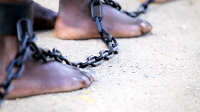 Slaves feet shackled together video