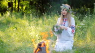 Slavic woman in an embroidered shirt patterns , weaves a wreath of wild flowers sitting by the fire . video