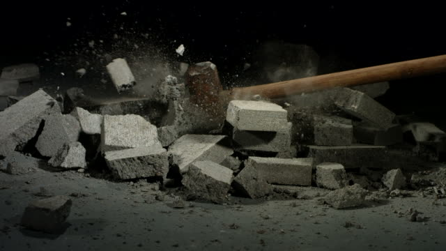 Sledge hammer hitting concrete bricks video