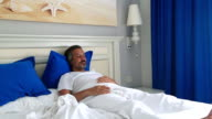 Sleepiness man in bed room watching television video