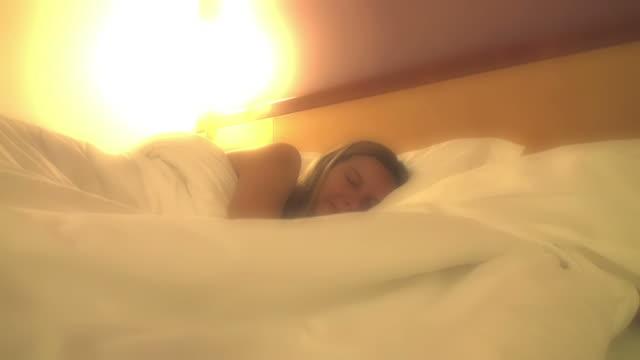 Sleeping woman awakening in a dreamy soft atmosphere video