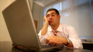 Sleepy businessman using laptop in office video