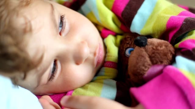 Sleepy little girl with toy bear lying in bed video
