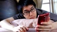 sleepy man with eyeglasses in bed woken by alarm on mobile phone video