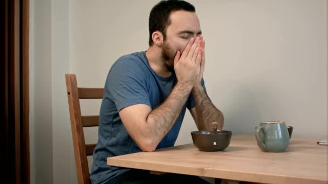 Sleepy man yawning at breakfast table video