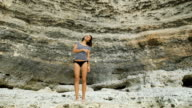 Slender brunette standing near a rock wall and enjoy your vacation at the resort. Girl dressed in a striped t-shirt, straightens her curly hair video