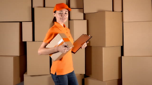 Slender girl in orange uniform delivering a parcel against carton stacks backround. FullHD studio video video
