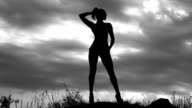 slender girl photo model posing for a photo shoot on the background of a cloudy sky on the field, black and white video, the silhouette of a woman video