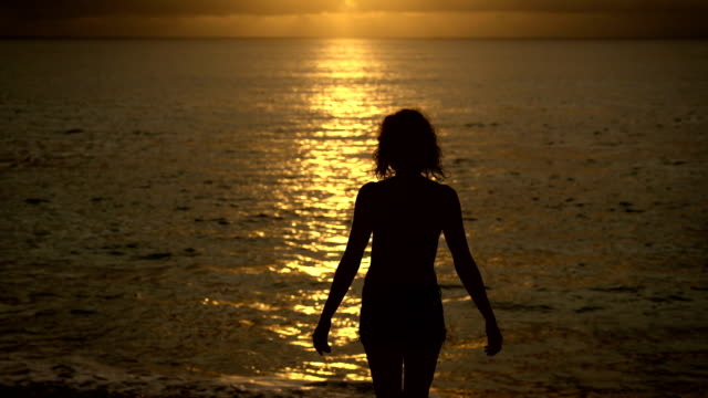 Slender girl slowly walks into the ocean at sunset to cool off. Silhouette of a young woman on a background of the sun reflections in the water, which raises hands up video