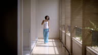 Slender girl walks along a long balcony of a hotel in the resort. At a young brunette wearing a white shirt and blue pants are falling the sun's rays through are not closed windows video