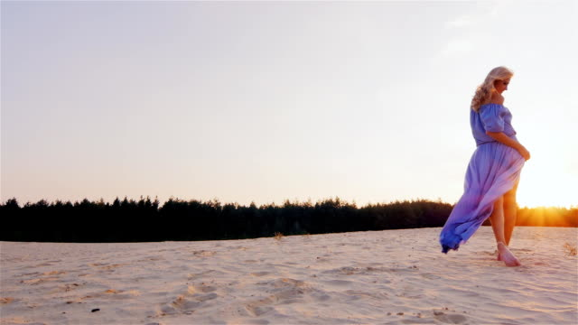 A slender woman in a light blue dress standing on the beach at sunset. The wind plays with her dress video