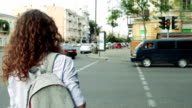 Slender woman with curly hair and a backpack waiting for the green traffic light at pedestrian crossing video