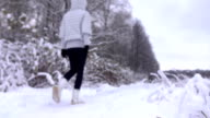 Slender young woman in grey jacket walking in a beautiful snowy winter forest FullHD shot video