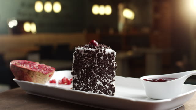 Slice of black forest cake with pomegranate and cherry topping on plate video