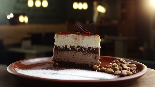 Slice of chocolate cake with cherry topping one plate with nuts, almonds and peanuts beside video