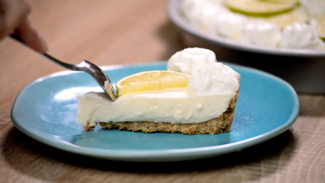 Slice of key lime pie with fresh limes and a garnish. Eat lime cake video