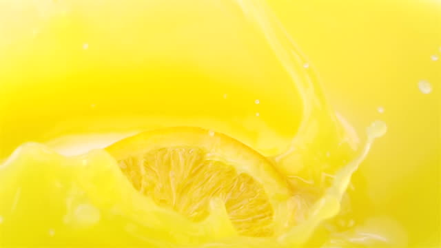 Slice of Orange Falling into Orange Juice. video