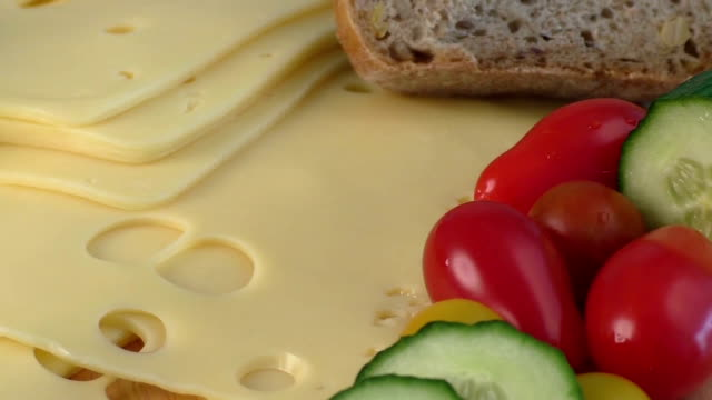 Sliced delicious edam cheese on wooden board video