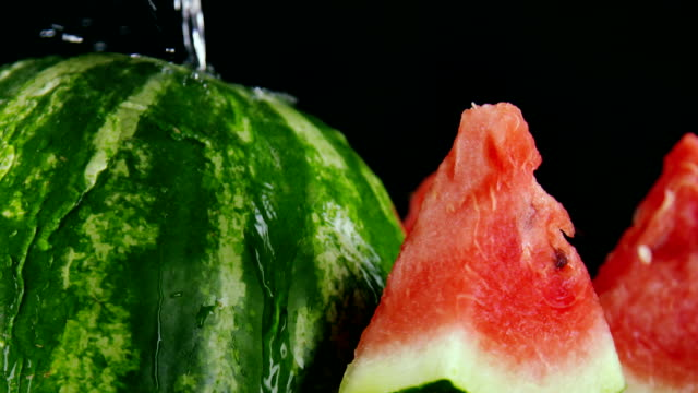 Sliced red watermelon with splashes of water in slow motion on black background video