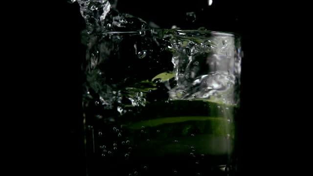 Slices of cucumber fall into the soda. Slow mo video