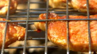Slices of grilled juicy pork steaks over coals, on the brazier, macro video