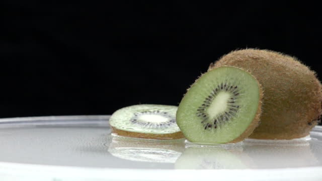Slices of kiwi fruit drops into water,slow motion video