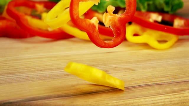 Slices of Ripe Peppers are Falling on Wooden Table. video