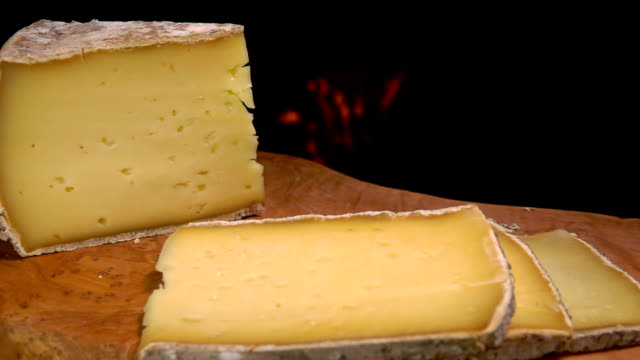 Slices of solid sheep cheese falling on a wooden board video