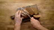 Slicing whole grain bread on wooden table, top view, video