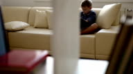 Sliding camera peeks in on a boy sitting on a sofa reading a book video