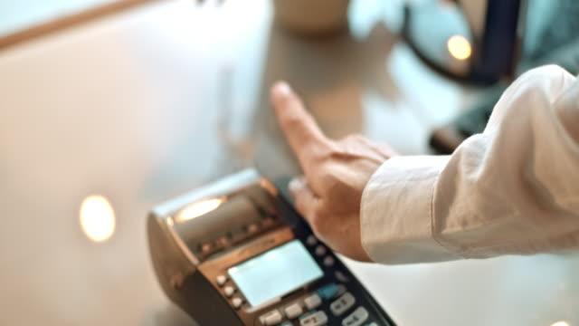 SLO MO sliding credit card through terminal and entering amount video