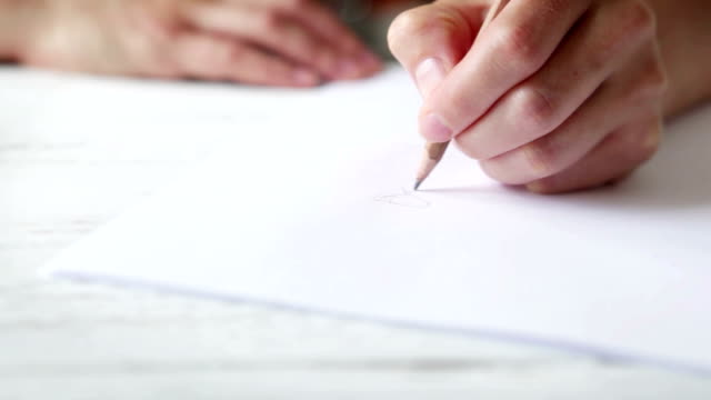 Sliding footage of an artist's hand sketching with a simple pencil video