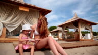 Slim, beautiful mom in bikini with her little daughter playing with a smartphone video