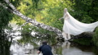 Slim blonde woman stands on birch above water surface video