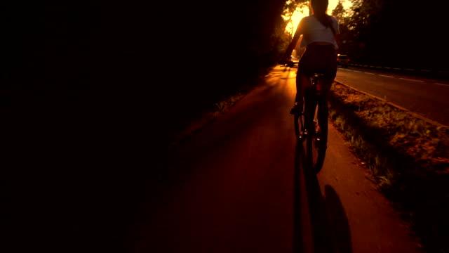 Slim brunette girl riding a bike along summer sunset road. Slow motion tracking shot video