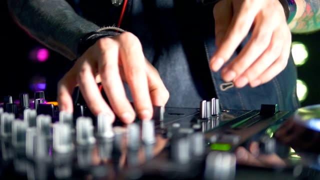 Slim DJs hands manipulate mixer console settings. video