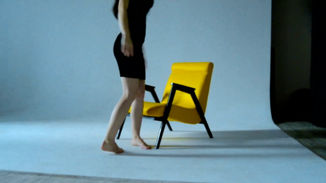 Slim girl in black dress sits down on a Chair in the Studio video
