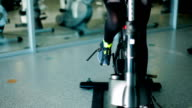 Slim sports legs pedaling on the exercise bike in the gym video