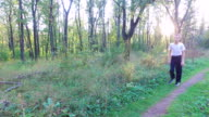 Slim teen boy goes along a path in the forest. The boy finished the training and goes away home. Sports in nature. Morning sun forest at dawn. video