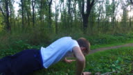 Slim teen boy is wrung out off the ground in the forest. Boy is trained to become stronger. Sports in nature. video