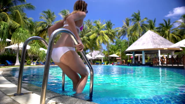 A slim young woman enjoying swimming in the pool on a tropical resort. Slow motion. video