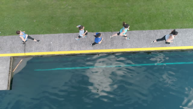 SloMo aerial view of women jogging next to a pond video