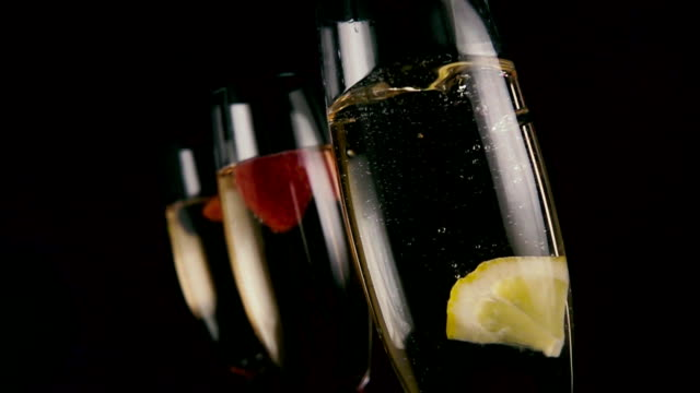 Slow mo. A slice of lemon drops into champagne video