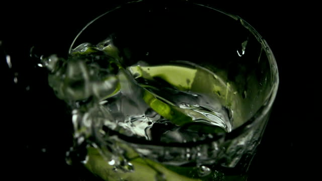 Slow mo. Cucumber and ice drops into a glass with cucumber water video
