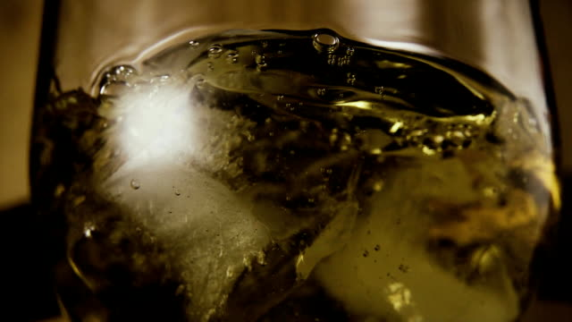 Slow mo. In a glass of brandy drops ice video